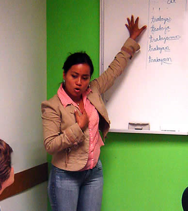Spanish teacher in classroom in front of whiteboard explaining a lesson